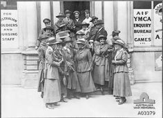 Nurses, soldiers and a male civilian standing on the steps of the YMCA, prior to leaving on an excusion to Windsor. Note the variety of hats the nurses are wearing. The nurse in the left foreground is wearing the colour patch of No 14 Australian General Hospital (AGH) in Cairo, indicating she is probably on leave. The nurse behind her is wearing a chevron on her lower sleeve denoting three years service.
