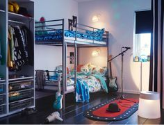 Um quarto de criança com um beliche prateado, com roupa de cama em turquesa e azul No chão, um tapete com iluminação LED, parecido com um palco