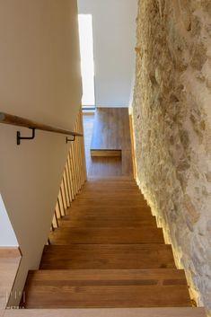 Escalera de madera iluminada junto a muro de piedra | METRIA Arquitectos