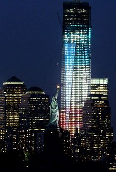 The iconic Statue of Liberty dwarfed by the rising One World Trade Center, lit up here in the colors of the American flag.