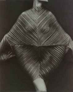 1990 - Wrapped Torso - To show off this dress by Issey Miyake, Herb Ritts selected a dark backdrop and had model Karen Alexander adopt a ballet-like pose. Lighted from above, the semitranslucent fabric both reveals and obscures the contours of the model's body. The photographer's choice of the platinum printing process over the less expensive and more common gelatin silver process gives the photograph a significantly wider range of tones and a luxurious matte surface.