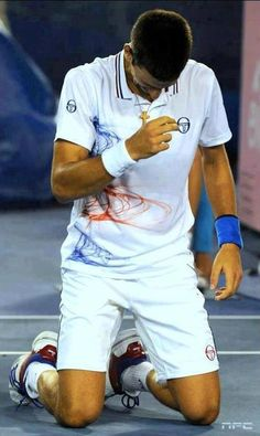 Novak Djokovic is making the sign of the cross.