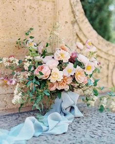 """""""The bride's bouquet included garden roses, Japanese anemones, and clematis recta vines that were tied together with a blue ribbon. To see more incredible…"""""""