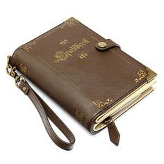 The Spellbook Wristlet is a compact tome which aims to help you convey your belongings. It has a see-thru ID slot and 14 additional card slots, one for each library card with a few left over for credit cards.