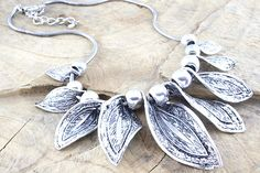 Chunky, twisted metal leaf necklace set on a snake chain.