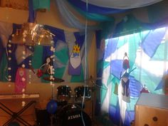 Adventure Time Party: Ice King's Castle. Backdrop made by cutting up 3 different blue, plastic tablecloths and hot-gluing them back together (this was insanely time consuming and frustrating and I will never do it again! :) ), cotton ball snow hanging from chandelier, and tent canopy on ceiling made with plastic tablecloths. Characters are princesses inside Ice King's jail, and they are made of construction paper.