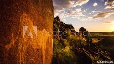 Stock Video of Static timelapse with a textured rock and a bushmen engraving on a hill with green grass in the foreground and the sun setting in the background with clouds moving towards the camera available on request. at Adobe Stock African Sunset, Green Grass, Windmill, Geology, Stock Video, Stock Footage, Monument Valley, Clouds, Sunsets