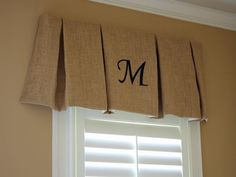 Inexpensive burlap is folded into deep box pleats and stapled onto a board to create an easy valance. The stenciled monogram adds even more detail.