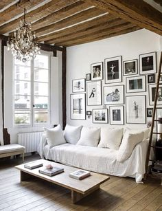 Chic living room with exposed beams, a large gallery wall, a white sofa, and a vintage chandelier