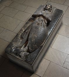 The tomb effigy is of Jean d'Alluye, a French knight of the thirteenth century. When he died in 1248, he was buried at the abbey he had founded—La Clarté-Dieu near Tours in northwestern France.  This type of effigy, showing the deceased lying atop his tomb, is known as a gisant. The knight holds his hands in prayer, and his expression is one of deep contemplation. Medieval knights combined Christian and military ideals and aspired to the virtues of piety, loyalty, and honor.