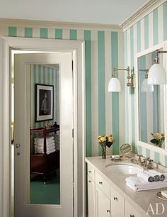 Sconces from Circa Lighting flank the master bath mirror; the walls feature hand-painted stripes, and towels are stored on a 19th-century trolley from Niall Smith Antiques.