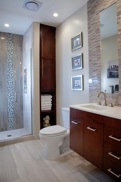 A custom-designed, floor-to-ceiling storage tower offers a mix of open and closed storage space in this contemporary bathroom. The bottom shelves were left open for easy access to towels, while the top shelves were fitted with doors for concealing toiletries. The compact, wall-mounted floating vanity saves space but still offers extra storage and style.