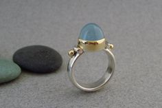 Cool grey blue. Deep smoky blue. The color of the sky after a storm.  A frosty grey-blue aquamarine with a high dome is set in a tall, 18k yellow gold bezel. The balls on either side of the stone are 18k gold as well, with the remainder of the ring in sterling silver. A heavy silver band makes this ring very comfortable. This unique stone measures 10 mm.  ***Aquamarine is a blue-green variety of beryl and the birthstone for March. Associated with the throat chakra, it is thought to ease…
