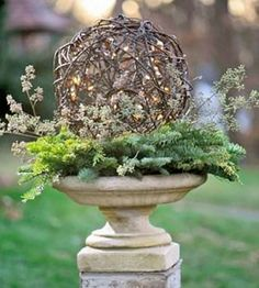 This birdbath is lined with a fresh pine wreath and topped with a vine ball. To add sparkle, thread a strand of battery-powered white lights into the ball. (BH)
