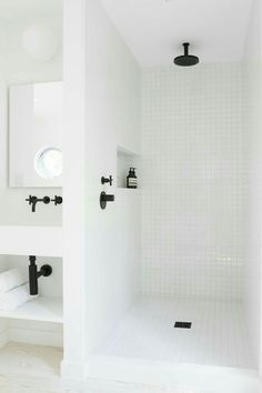 Black accents white tile shower and white walls