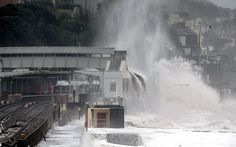 As storms batter Britain, dragging part of the coastline into the sea, forecasters have warned that the worst is yet to come. The sea wall and parts of a railway station crumbled under as strong winds and huge waves battered the coast in Dawlish, Devon. Here, water cascades from the roof of Dawlish station as the sea engulfs the rails