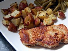 Two-Packet Pork Chops and Ranch-Roasted Potatoes: 8 baby red potatoes, quartered, 2 Tablespoons butter, 2 Tablespoons olive oil, Salt and pepper to taste, 4 boneless pork loin chops, 1 packet onion soup mix, 1 packet ranch dressing mix divided, 1/2 cup flour