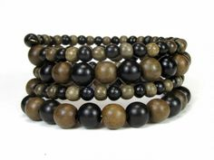 * * Coiled memory wire bracelet with graywood beads and ebony wood beads * Graywood beads are both 8mm and 5mm * Ebony wood beads are both 7-8mm and 5-6mm  * Wood beads come from the tropical forests