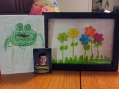 "Framed button flowers for teacher gift.  Buy a 5""x7"" wooden picture frame, cut a piece of paper to 5""x7"", have your child draw grass and stems with leaves, glue button flowers at the tops of the stems. I used small pieces of cork board (use whatever you have that will work) to raise the frame away from the backing to give it a shadow box effect. Attached a school picture and had son make a handmade card with his own special message in it."