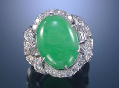 JADEITE AND DIAMOND RING, 1930S.  The central oval cabochon jadeite within a mount of radiating geometric design set with single-cut and baguette diamonds, size N ½, accompanied by a case from Harrods, London.
