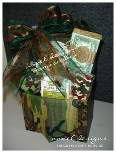Survival Gift Basket includes camo gear like Stress Ball, Deck of Playing Cards, Aspirin, Pretzels, Chocolate Bar, Nuts & Vitamin Enriched Water arranged in a camo gift basket box decorated with a camo bandanna.