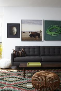 There's something really nice about the darkness of the grey sofa and artworks.  Maybe it's that they all look matte.  Paired against the muted greys and reds and beiges in the killim rug and thgrow pillow, and the small pops of color, this space looks very sophisticated and warm.