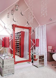 OVER. THE. TOP.    Girly pink walk-in closet with vaulted ceiling, pink walls paint color, mirrored tables flanking glossy red lacquer floor mirror, glass lamps with red shades and red shoe shelves.