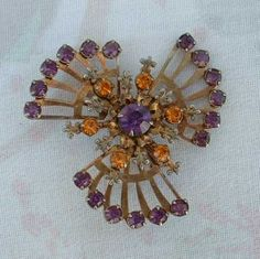 This fabulous pin has small fleur-de-lis symbols above or between each topaz-colored rhinestone, and an outer perimeter of amethyst rhinestones, plus a large chaton-cut amethyst in the center. All of the rhinestones are prong set, and are open in the back. The metal has a copper wash on it, giving the whole pin a warm glow. The brooch has about a 1-3/4 inch diameter, and is in excellent condition. Beautiful pin, for all seasons! It will be shipped in a gift box.