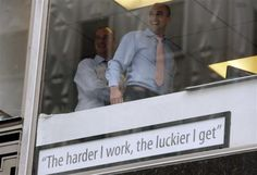 Businessmen in a window laugh after placing a sign on their window above where Occupy Wall Street protesters were marching along East 42nd street in New York, May 1, 2012.   REUTERS/Mike Segar