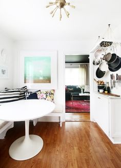 White and bright kitchen with small breakfast nook, hanging pots and pans, modern chandelier and beachy art