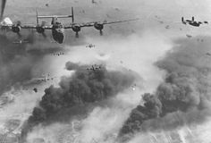 """Through flak and over the destruction created by preceding waves of bombers, these 15th Air Force B-24s leave Ploesti, Rumania, after one of the long series of attacks against the No. 1 oil target in Europe."" (National Museum caption)"