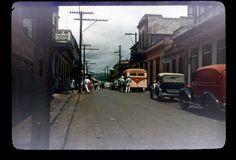 Aibonito street scene, vehicles parked, people walking in street, buildings built up to sidewalk | 1940s