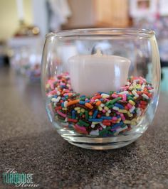 DIY  Party Decor :: Place a votive candle in a jar with some colorful sprinkles.....cheap and easy grad party table lights