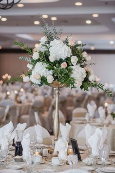 Peach, sage green and gold wedding color palette. Tall centerpieces consisting of white hydrangea, cream and peach roses, and lush greenery by Kari Dawson Photography