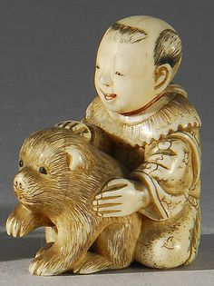 Lot 61: IVORY NETSUKE In the form of a boy playing with a puppy. Signed. - Eldred's | Invaluable