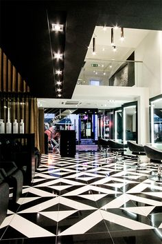 The decor of this modern elegant beauty salon creates a sense of luxury through the use of black and white tile patterns.  The interior design is sophisticated with its use of bronze sheer curtains to create private treatment rooms. Other decor ideas are the use of sleek styling stations giving a boutique hair salon ambience. | #floor | #bronze | #designer |