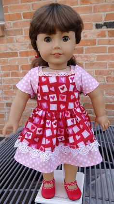 This dress has been made to fit 18 dolls like American Girl. Your doll will love wearing this dress for Valetines Day this year. I used a valentine print and a pink polk-dot cotton as an accent. The skirt has a double layer with pretty venise lace on the first layer. The dress closes in the back with two working buttons on the bodice. I added a matching bolero style jacket. American Girl, Molly is modeling this dress for us. Doll and shoes are not included, but I will include the hair…