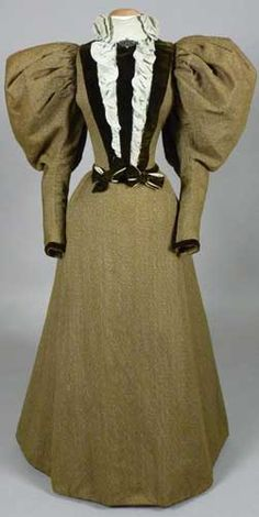Wool tweed day dress with silk crepe and silk velvet decoration, 1894-95. The huge sleeves, ruffled bodice front, and wide skirt create an optical illusion, making the waist seem extra tiny. While this waist is quite small (21 1/2 inches) it is not out of proportion for the petite woman (about 5 feet) who wore it.