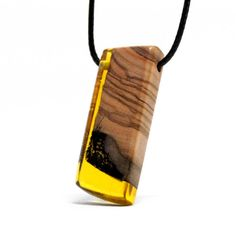 This unique pendant is made from naturally dried olive wood and UV resistant epoxy resin. Hand sanded to the highest grit, it is very pleasant to touch and easy to the eye. Nice glossy aspect without any varnish or oil applied.  If needed, you may clean this pendant with a soft cotton cloth wet or dry. Avoid using acetone or alcohol as these will attack the epoxy and ruin its aspect.  -------------------------------------------------------------------------------------------  Pendant…
