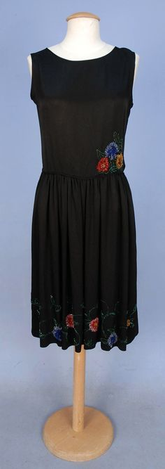 BEADED EVENING DRESS, 1920's. Sleeveless black silk having set-in waist with self piping and gathered skirt with colorful beaded floral at hem and floral cluster at waist.