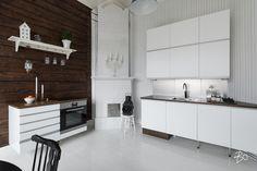 Keittiössä valkoiset Kvik-kaapistot massiivitammitasoineen ja rauhaisa värimaailma ovat hyvä vastakohta korkeuksiin nousevalle kaakelikakluunille, vanhoille hirsiseinille ja kauniin harmaille lankkulautalattioille.