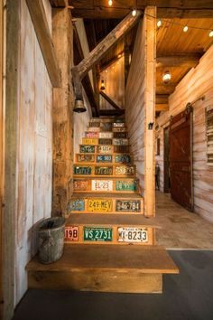 Rustic Cabin Decor - Vintage license plates add pops of color to the staircase that leads to the loft area.