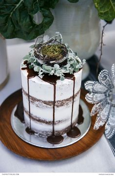 This semi-naked cake, dripping with chocolate and covered in delectable icing, will grab your guests' attention and delight their palates! | Photographer:Charl du Preez | Stylist:Nicky Myburgh | Confectionery: Soefija's | Nest: Green Lily Landscaping | Wooden Plate: ARK Workshop