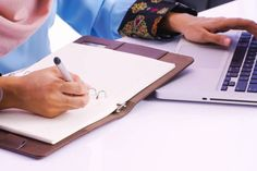 business woman writing on notebook while other hand searching on