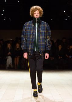 A navy tartan bomber jacket layered over a deep green tracksuit jacket, slim-fit tracksuit trousers and The Sneakers in black and burnt yellow. Discover the collection at Burberry.com