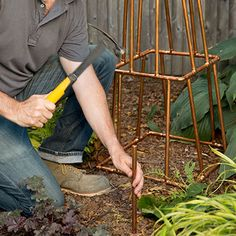 Select a spot for a garden trellis: Make a hole with a garden stake, then tap the first leg into the soil, as shown. Set the trellis on the first leg and use it as a guide to position the remaining legs. Tap them in place, adjusting their height as needed to get the structure to stand plumb.