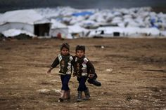 Syrian boys, whose family fled their home in Idlib, walk to their tent, at a camp for displaced Syrians, in the village of Atmeh, Syria, Monday, Dec. 10, 2012. (AP Photo/Muhammed Muheisen)