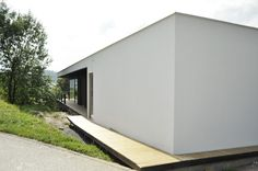house on a slope, white fasade, black charred boards / by MOAD architects
