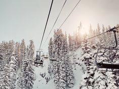 Beautiful landscape photography taken from a ski resort chairlift of the sun shining through the clouds across a snowy mountain side, with snow covered pine trees