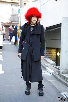 This is Masaya, a 20-year-old guy often seen around Harajuku lately. He is wearing a black outfit with his signature red furry hat and red hair. Masaya's outfit is mostly from his favorite shop, AnkoRock, including his coat, skirt, bag and lace-up boots. He is also wearing a fringed Algonquins shirt, a studded choker and other necklaces, as well as several rings. Masaya mentioned that he's a fan of the Japanese visual kei / J-rock band The Gazette. (Tokyo Fashion, 2014)